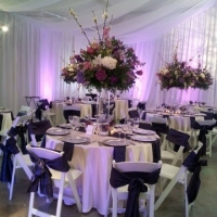Elegant Tablescape With White Chairs and Sashes